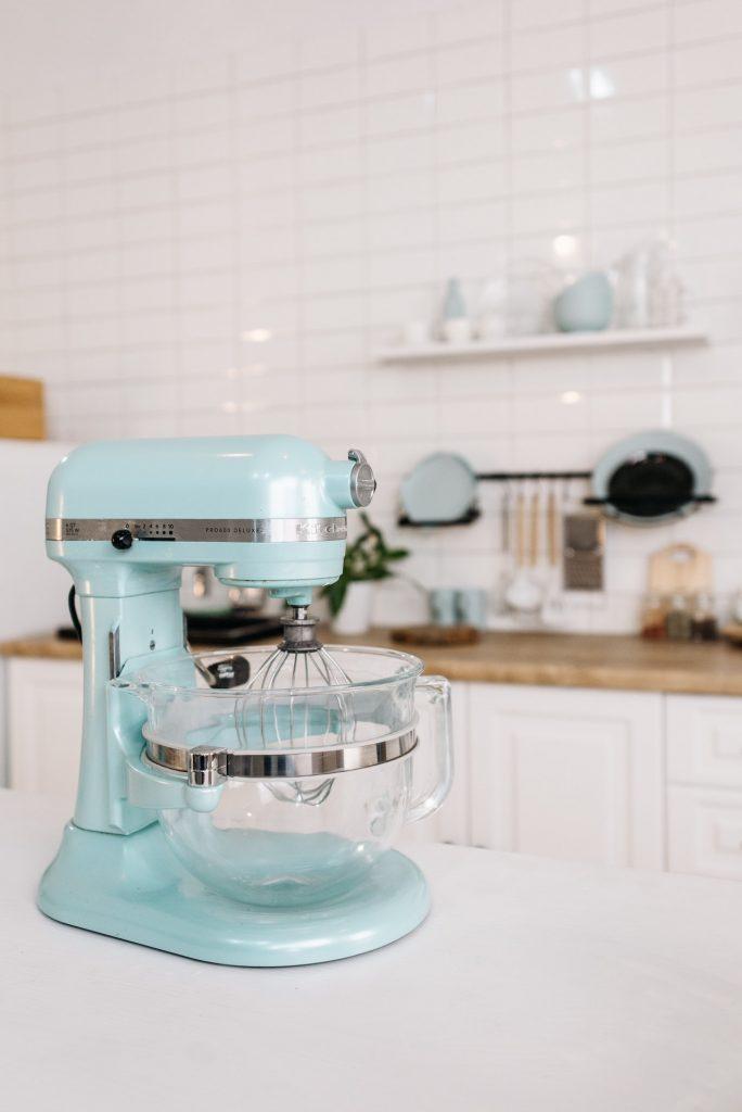 A teal Kitchen Aid mixer on a white kitchen countertop.