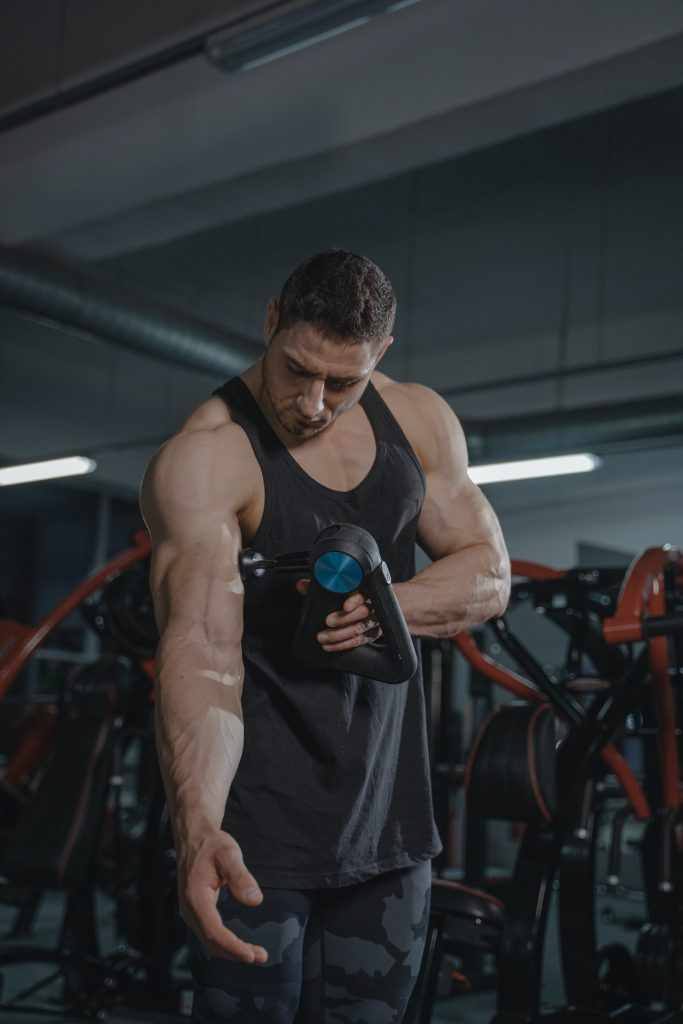 Man at gym using  a powerful massage device on his bicep muscles.