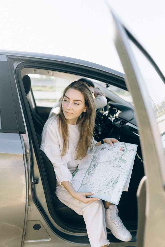 Woman sitting in car looking at a map.