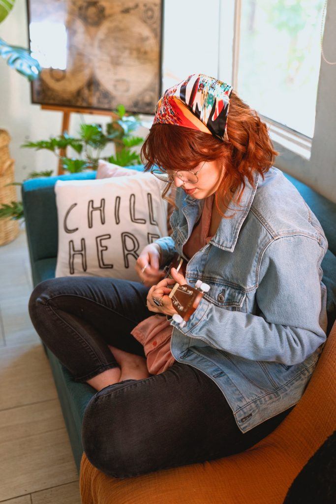 Woman with red hair and wearing a jean jacket sitting on a couch playing a ukulele.