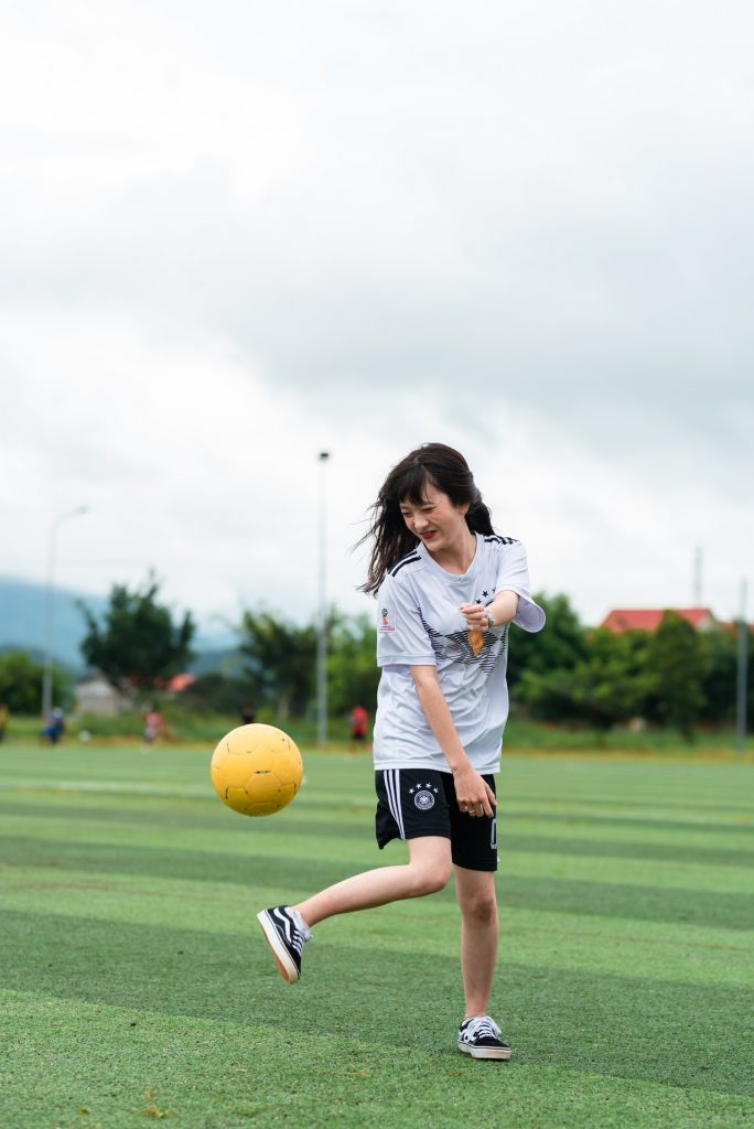 Woman kicking a yellow soccer ball outside.