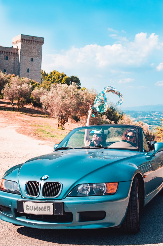 Two women in a BMW z3 with the top down.