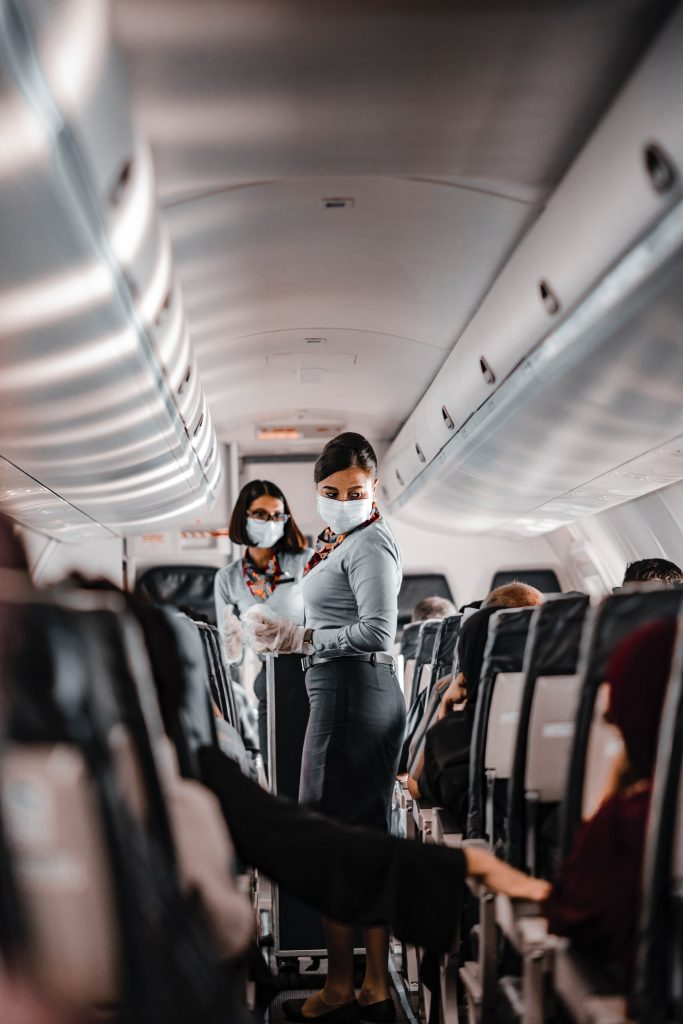 Flight attendants on a full plane during the COVID-19 pandemic.