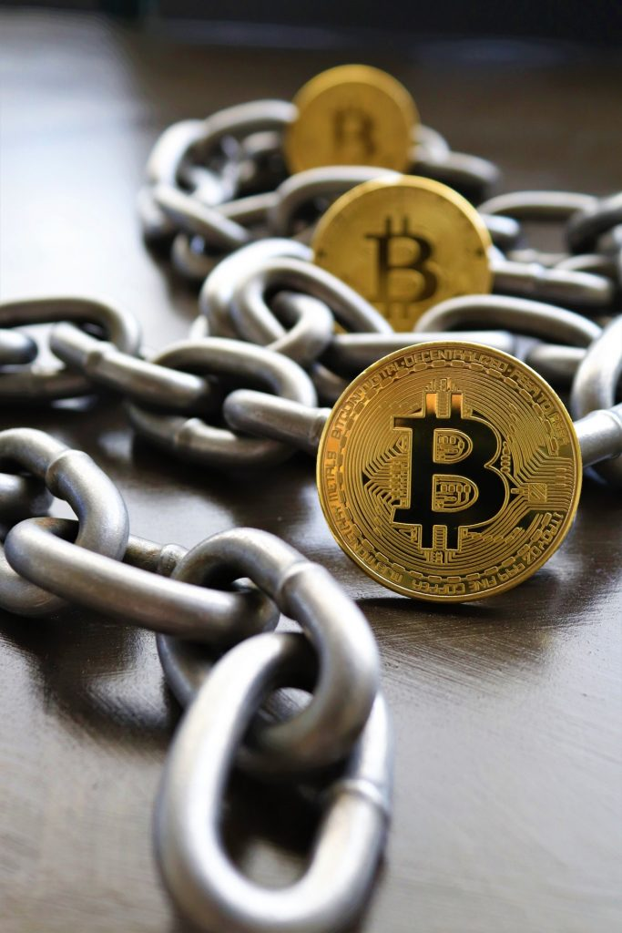 A chain and bitcoins laid out on a table to represent blockchain technology for cryptocurrency trading.