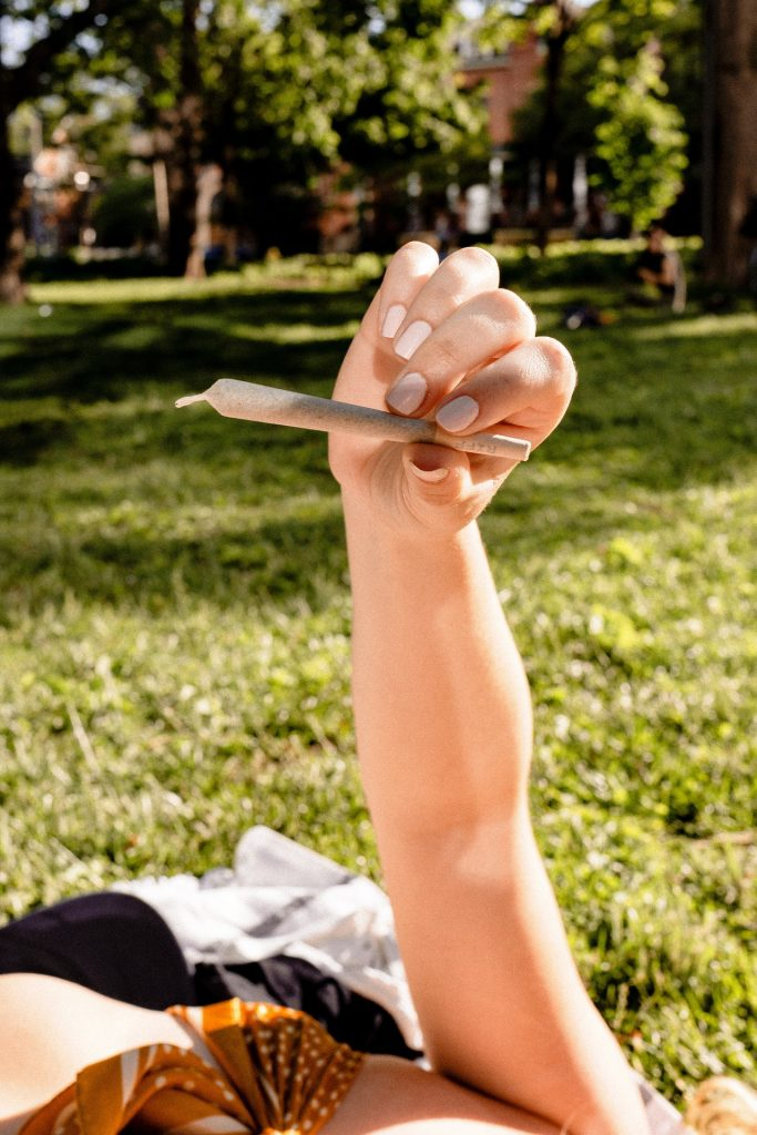 Woman holding up a joint while laying in a park.