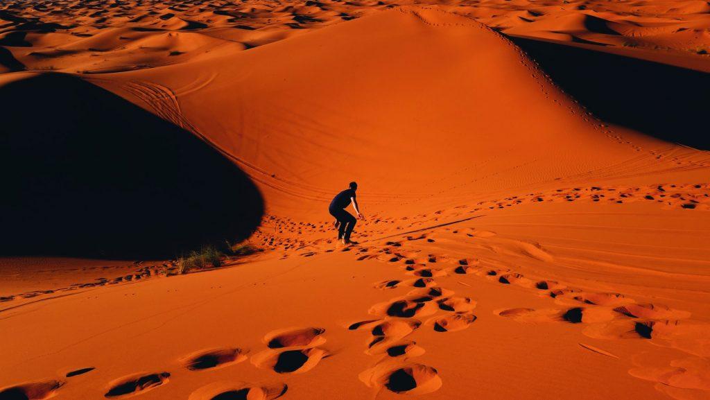 Man sand surfing in the Sahara Desert.