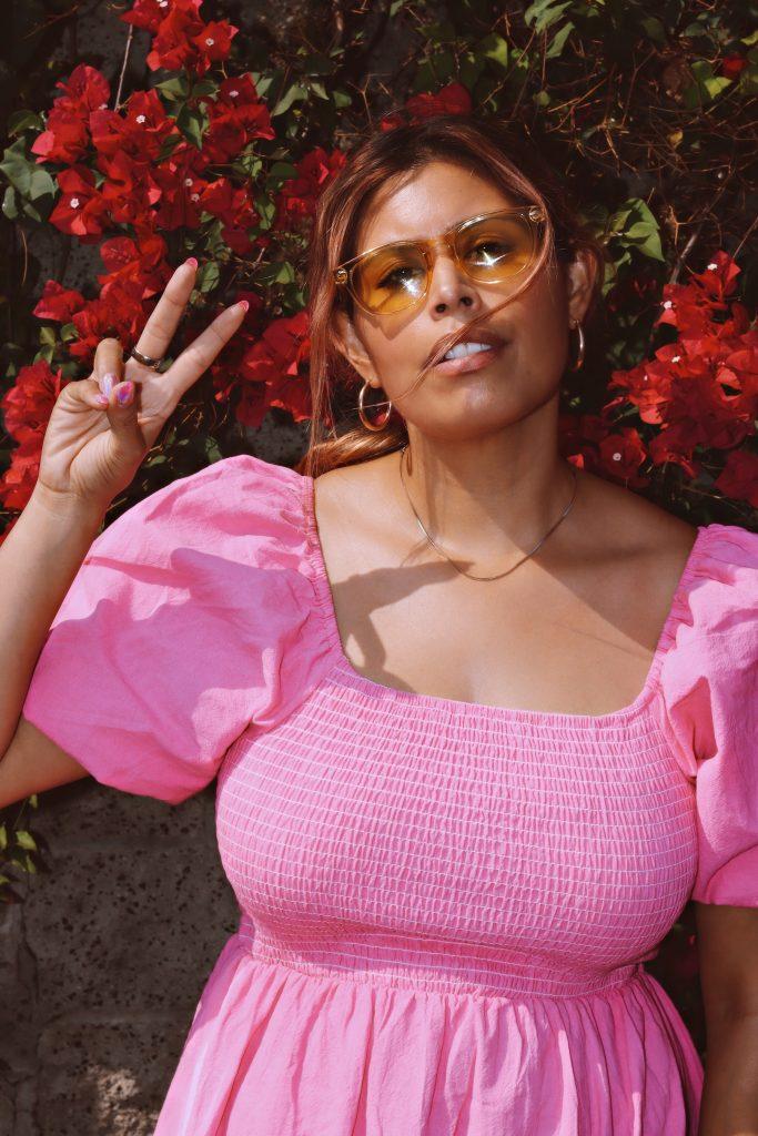 LA blogger Amanda Raye Scozzafava of Broke & Chic giving a peace sign in a pink split-hem dress from SHEIN in Pasadena, CA.