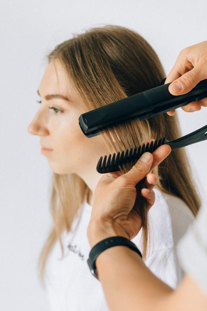 Hair stylist straightening a clients hair.